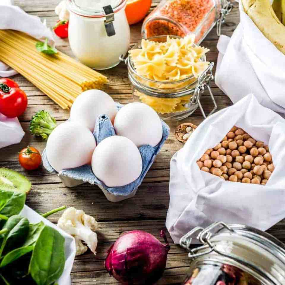 Healthy cheap budget friendly foods, like gluten-free pasta, eggs, beans, broccoli, tomatoes, and lentils on a wooden kitchen table.