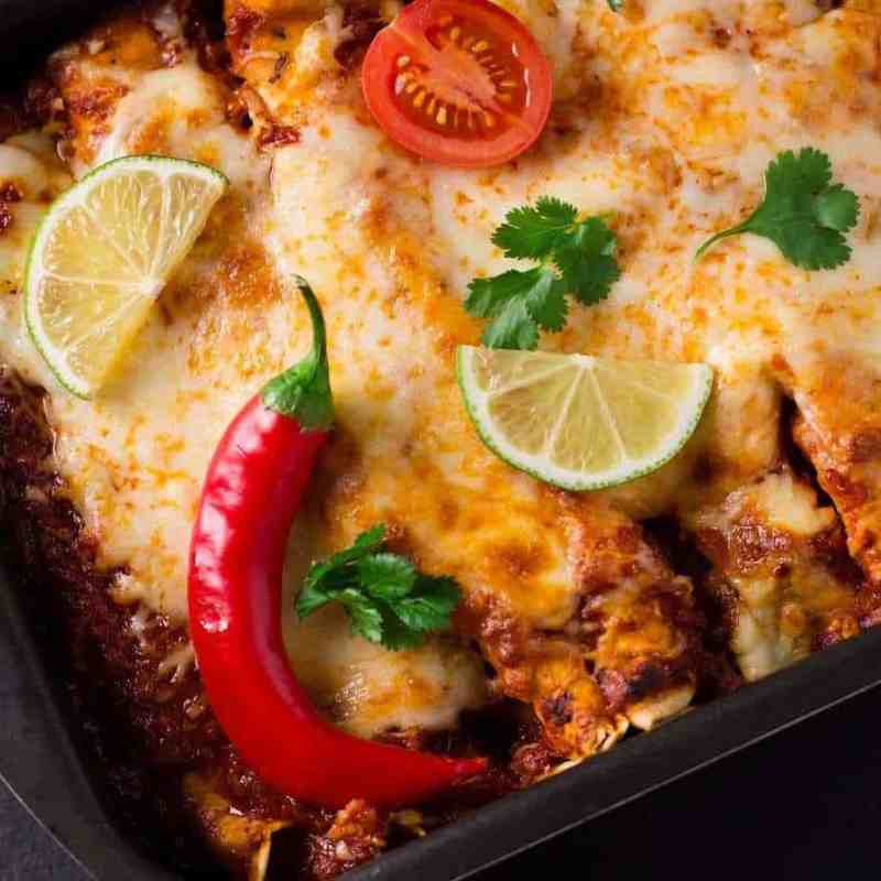 Sweet potato chicken gluten-free enchilada casserole topped with fresh lime, peppers, and tomatoes.