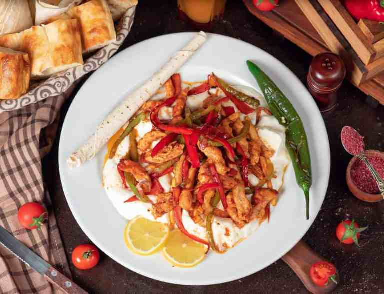 Chicken fajitas on a white plate.
