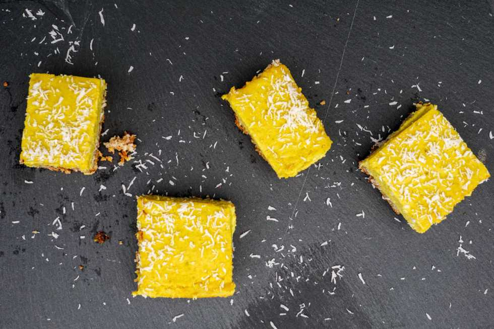 4 paleo turmeric lemon bars decorated with dessicated coconut on a black slate background