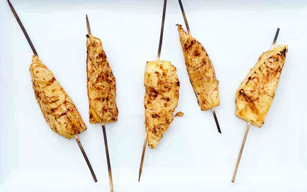 5 cinnamon dusted pineapple skewers, grilled, on white background