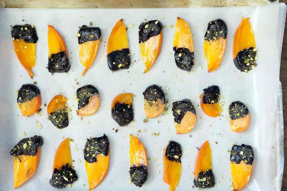 The flavors of buttery cinnamon persimmons, bittersweet chocolate, and freshly crushed pistachios make this quick, tasty and impressive dessert. Chocolate covered persimmons use just 5 ingredients, are ready in just a few minutes, and are sure to impress both your sweet-tooth and health-kick friends.