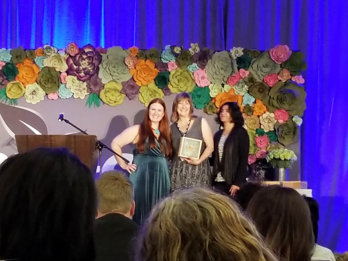 Three women holding an award for helping shift the community to safer products at ShiftCon Media