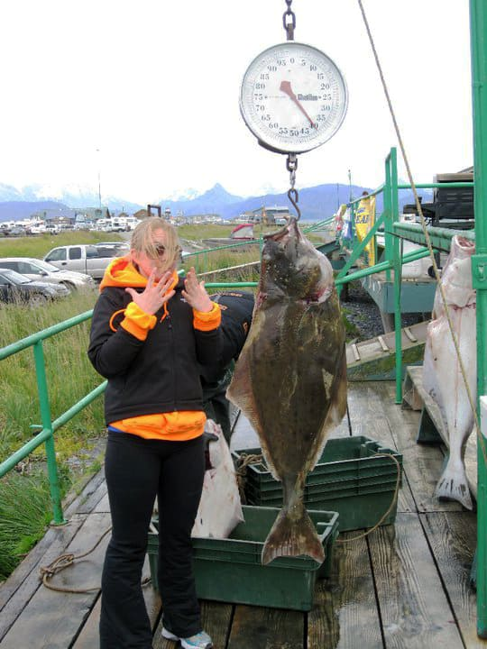 blond girl shocked at halibut catch