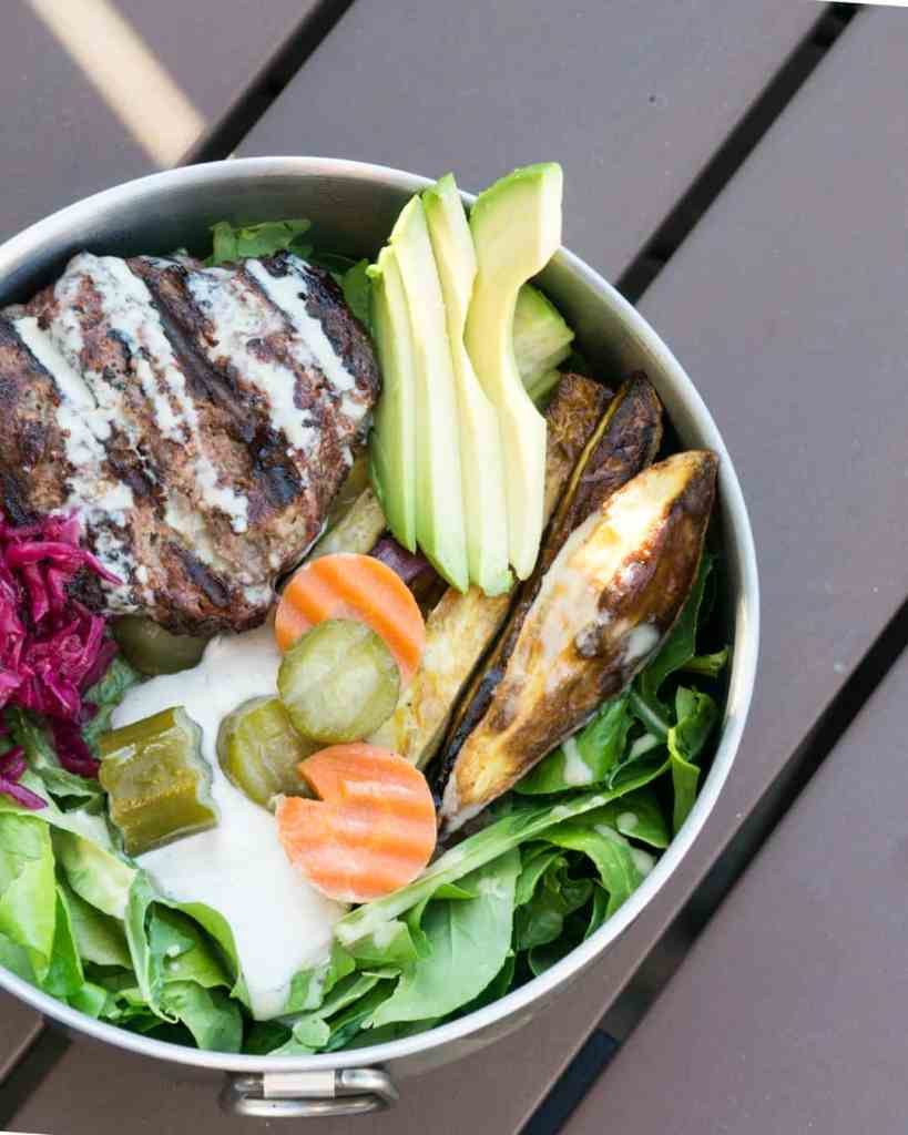 Paleo Elk Burger Bowl in Tin bowl on wooden picnic table: mixed greens topped with cashew cream, pickled cucumbers and carrots, roasted sweet potato fries, red sauerkraut, elk burger and tahini