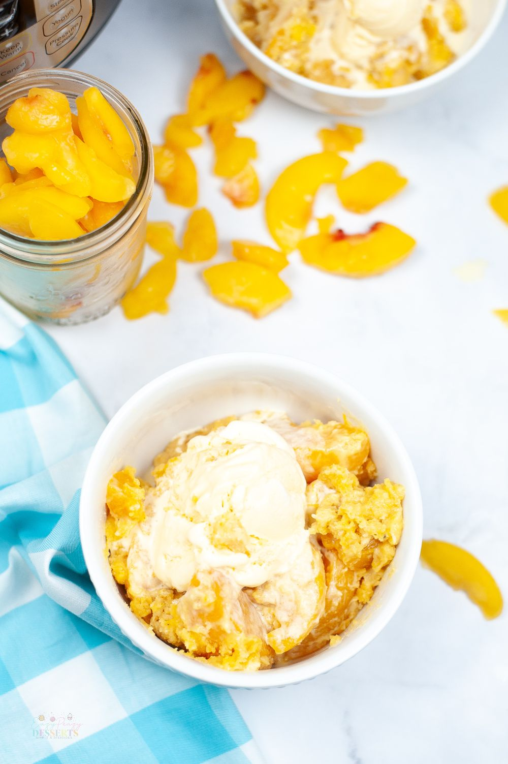 Image of instant pot peach cobbler in a white bowl, topped with vanilla ice cream