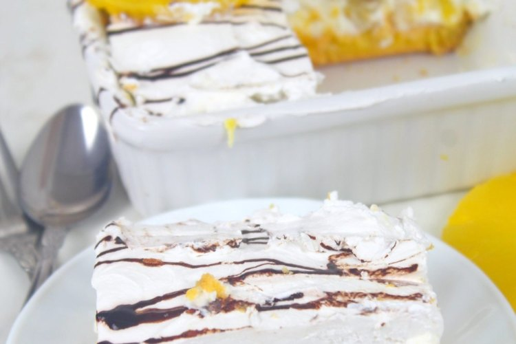 Image of a slice of no bake banana split dessert in a white plate next to a white baking dish filled with the rest of the dessert