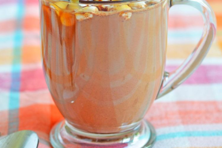 Spiked hot chocolate in a mug, decorated with marshmallows and chocolate syrup and caramel syrup