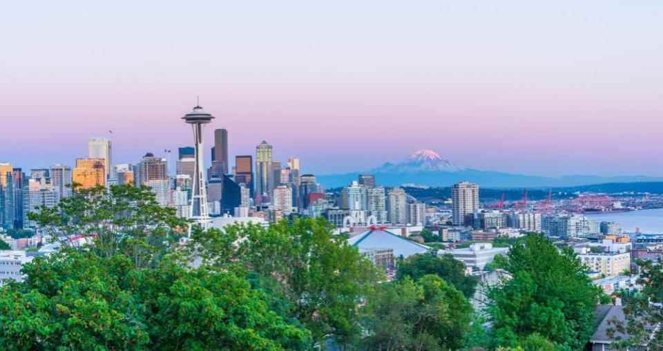 Downtown Seattle, Washington skyline highlights the Space Needle with snow-capped Mount Rainier seen in the distance.
