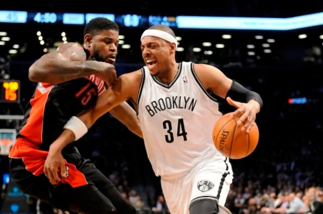 Brooklyn Nets' Paul Pierce (34) drives the ball around Toronto Raptors' Amir Johnson (15) in the first half of an NBA basketball game on Monday, March 10, 2014 at Barclays Center in New York. (AP Photo/Kathy Kmonicek)