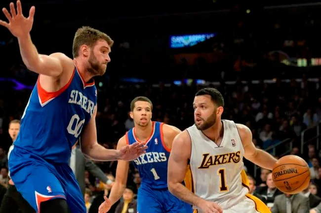 Dec 29, 2013; Los Angeles, CA, USA; Philadelphia 76ers center Spencer Hawes (00) defends against Los Angeles Lakers point guard Jordan Farmar (1) during the third quarter at Staples Center. Mandatory Credit: Richard Mackson-USA TODAY Sports