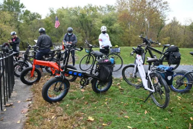 A group of ebikers standing near bicycles