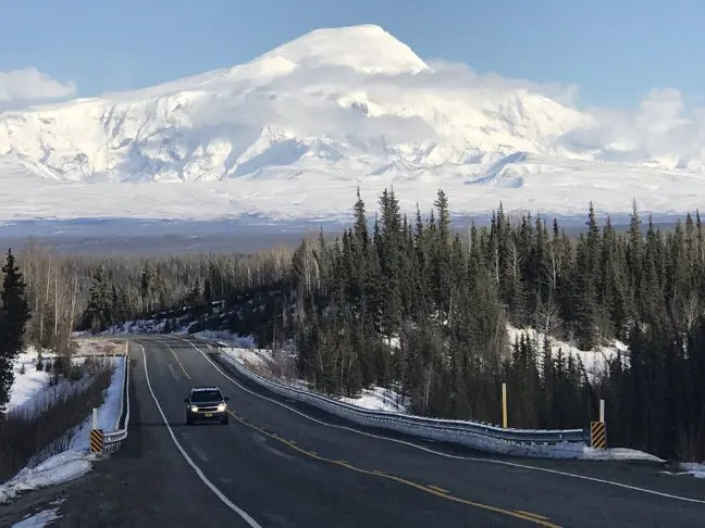Mount Sandford in Alaska in the background and an asphalt road in forests in the foreground