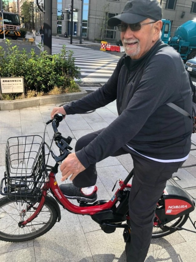 An older e-biker on a small e-bike that are available to rent in Tokyo, but they aren't very big!
