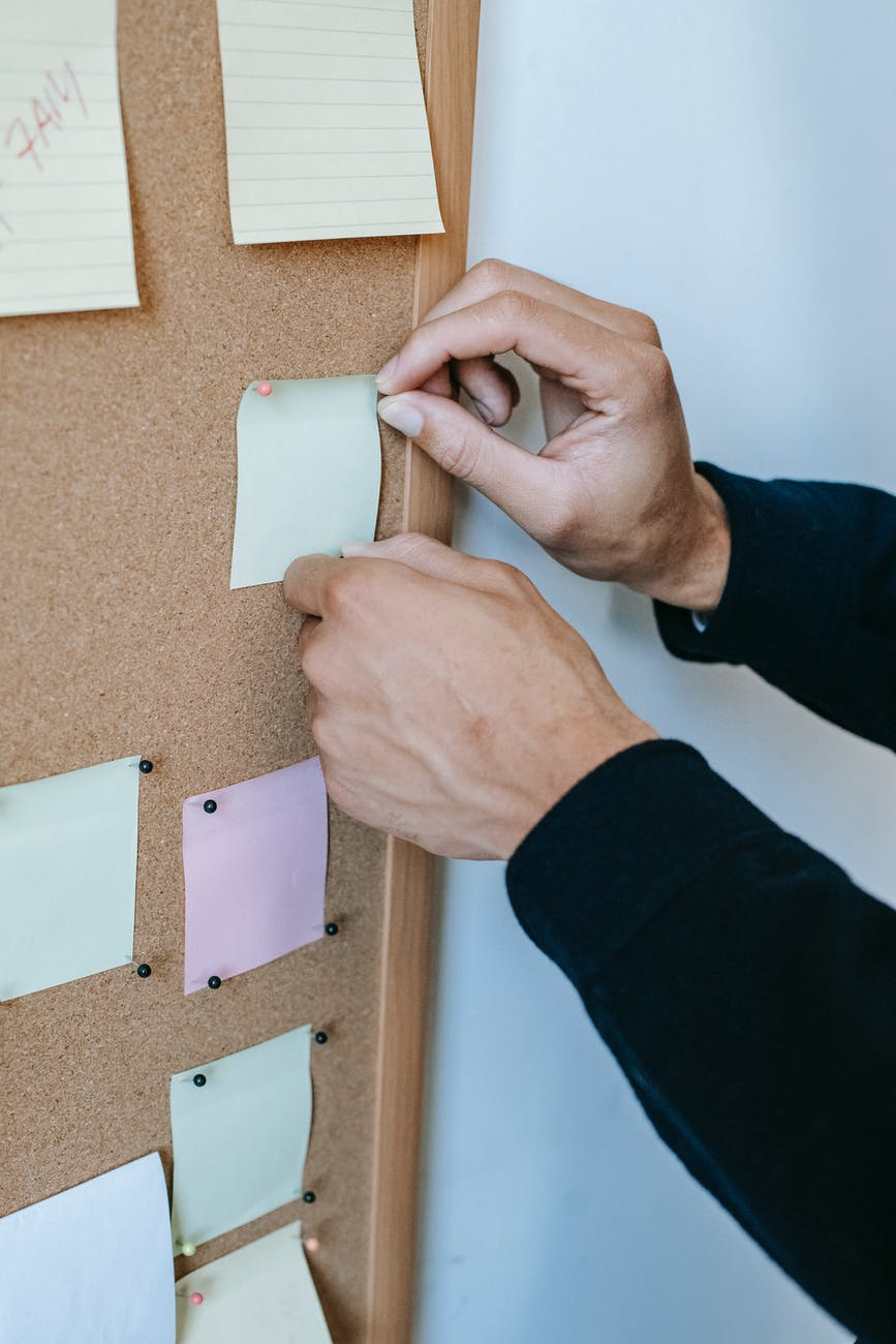 faceless man pinning memo papers on noticeboard