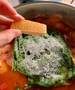 Add the frozen spinach and toss in a parmesan rind for extra flavor