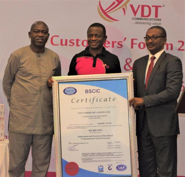 MD/CEO of VDT Communications, Biodun Omoniyi (middle), receiving the ISO 9001:2015 Quality Management System Certificate from Mr. Demiji Folami, the BSCIC ISO 9001 Certification auditor, while Mr. Tokunbo Talabi, a Director at VDT looks on