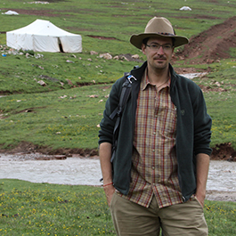 John Matthews stands in front of summer tents for a family of indigenous yak herders in the eastern Tibetan plateau in Qinghai Province, China.