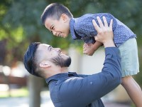 Albert Diaz lifts up his son Gabriel and the two laugh.