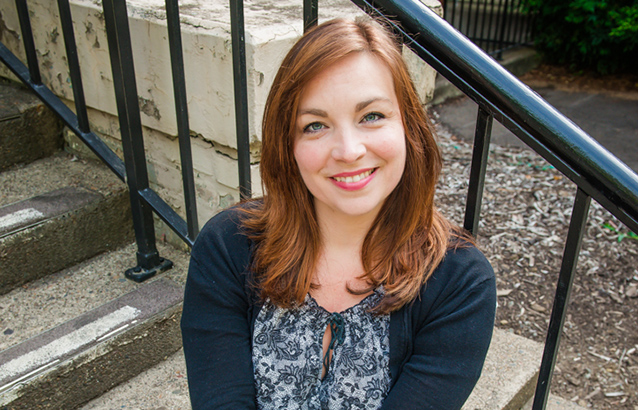 Amy Theis sits on gray stone stairs and leans against a black handrail.