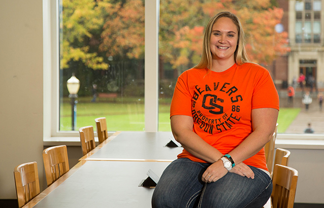 Bethany Ulman, wearing a bright orange Oregon State University Beavers t-shirt, sits on a table in the Valley Library on campus.
