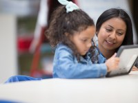 Brenda Contreras is kneeling next to a student in the elementary school classroom where she teaches as part of Oregon State's Master of Arts in Teaching program. The child wears a blue denim jacket and has long, dark and curly hair. Both are looking at a learning tablet that the student is holding.