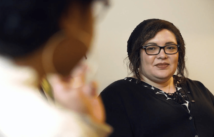 CSSA alumna and faculty member Kim McAloney sits in conversation with a colleague who is out of focus in the left side of the frame. Kim is in focus, and wears a black and white shirt and black cardigan; she is smiling slightly as she listens to her colleague.