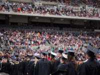 Reser Stadium is packed with graduates in their black caps and gowns and an audience of graduates' families at commencement 2016.
