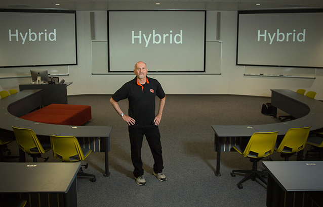 "Cub Kahn stands at the front of a classroom with two long, curved tables at the front. Behind him, three projector screens on the wall read ""Hybrid."""
