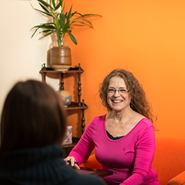 Dawn Marie sits across from someone smiling. Behind her is an orange wall and a corner shelf with a plant and small trinkets on it.