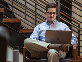 Eric Broadfoot, who earned a B.S. in Economics online with Oregon State Ecampus, sits with a laptop on his crossed legs.