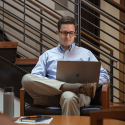 Eric Broadfoot sits in an open seating area near a set of stairs. He has one leg crossed over the other knee and looks down at a silver laptop in his lap. In front of him, a notebook and pen rest on a coffee table.