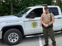 Evan Huegel wears his work uniform and stands in front of his Department of Natural Resources law officer truck.