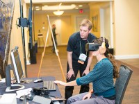 A member of the Oregon State Ecampus staff helps demonstrate a virtual reality assignment to an attendee of the faculty forum event.