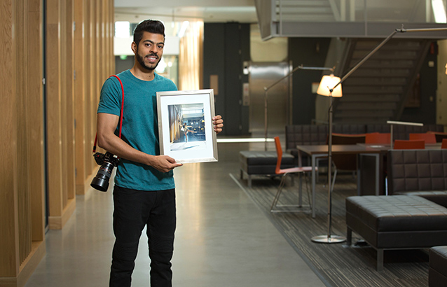 Hussain Al Balushi holds his framed winning photo and a camera hangs from his right shoulder on a red strap.