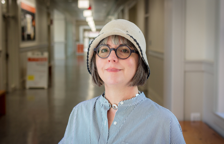 Jenny Sasser stands in a long hallway and smiles. She has chin-length grayish brown hair and wears small, round black glasses; a striped button-up shirt; and a beige knit cloche hat with a black brim.