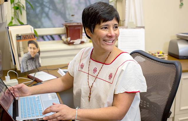 Ecampus Spanish Senior Instructor Loren Chavarría-Bechtel, sits at her neat but homey desk. She looks over her shoulder and smiles.