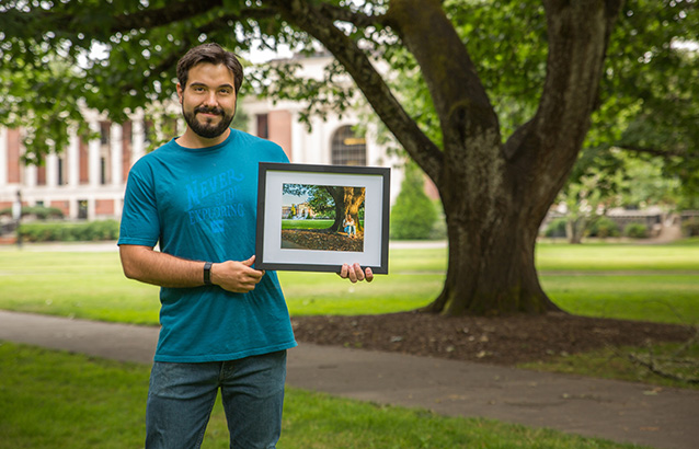 Lucas Kopecky Bobadilla, a master's student in crop science, holds his framed winning photo in the Memorial Union quad.