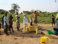 A group of people stand around a water pump that is surrounded by large yellow jugs. One person is pumping water into one of the jugs.