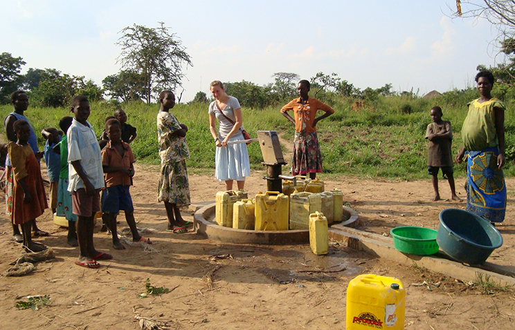 A group of people stands around a water pump while one person pumps water into yellow jugs.