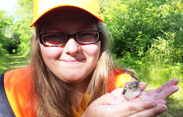 Megan Blackwell, an Oregon State Ecampus fisheries and wildlife student, holds a small warbler bird in her open palms.