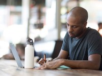 A man writes on a paper next to his laptop while sitting at a table inside a coffee shop. Online learning