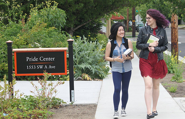 Two students walk together, smiling and holding books, near the walkway to the Oregon State University Pride Center, which serves LGBTQ+ students.