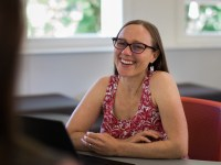 Oregon State instructor Raven Chakerian is seated in a red office chair in front of a wall with two large windows. She wears a red and white patterned sleeveless shirt, and she holds her arms loosely crossed on the table in front of her.