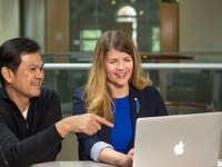 Rayne Vieger collaborates with Kok-Mun Ng, an Ecampus faculty member in the College of Education. The two sit together at a table with a silver laptop open in front of them.