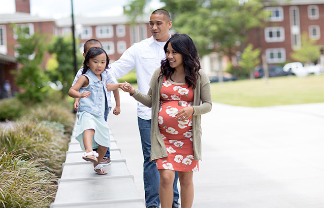 Samantha Diaz and husband Albert Diaz walk together. Each holds the hand of one of their children, who walk along a wide, waist-high ledge.