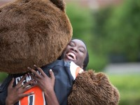 Secota hugs Benny the Beaver at Oregon State's campus before walking in the 2017 commencement ceremony.