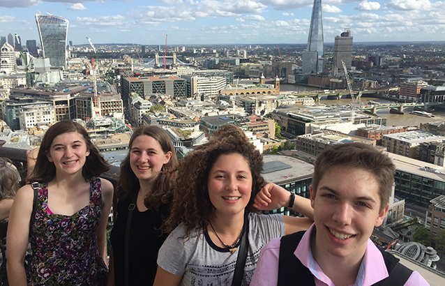 Four students stand with The Shard and other London buildings and skyscrapers in the background.