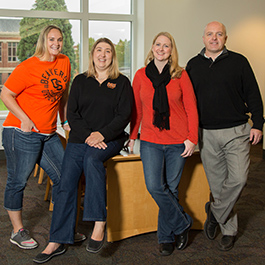 Four members of the Oregon State University Ecampus student success team pose together in orange and black clothing.