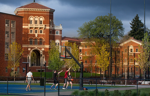 Four students play basketball on the intramural courts on campus with Weatherford Hall in the background.